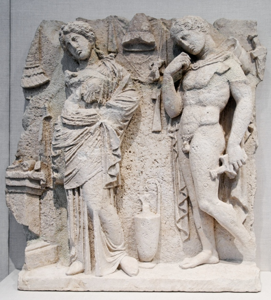 Tarentine funerary relief of a woman and warrior standing near an altar. c315 BC Photo by Marie-Lan Nguyen (2011)  released under Creative Commons Attribution 2.5 Generic