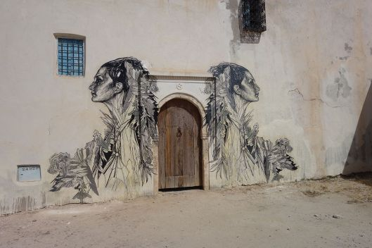"""Djerba Er Riadh Street Art 03"" by Rani777- Baha-Eddine MKD - Own work. Licensed under CC BY-SA 4.0 via Wikimedia Commons - https://commons.wikimedia.org/wiki/File:Djerba_Er_Riadh_Street_Art_03.JPG#/media/File:Djerba_Er_Riadh_Street_Art_03.JPG"