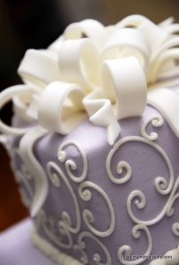 Lavender_wedding_cake_with_cream_white_swirls_and_ribbon_as_topper